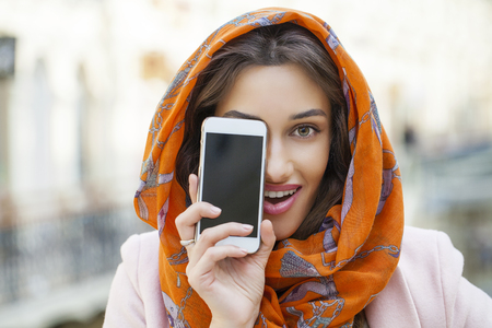 one eye: Close up portrait of a muslim young woman wearing a head scarf calling by phone Stock Photo