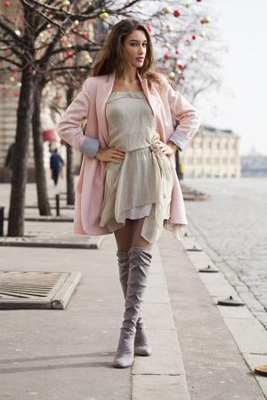 Portret in volle groei, sexy jonge brunette vrouw in roze jas