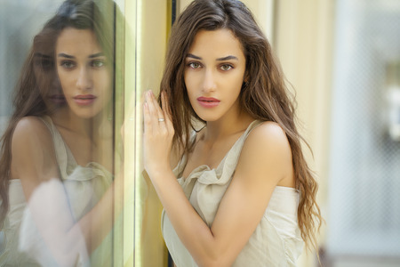 specular: Portrait close up of young beautiful brunette woman in beige dress, Specular reflection in a shop window