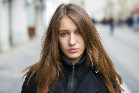 calm woman: Portrait close up of young beautiful brunette woman in black coat, on spring street background