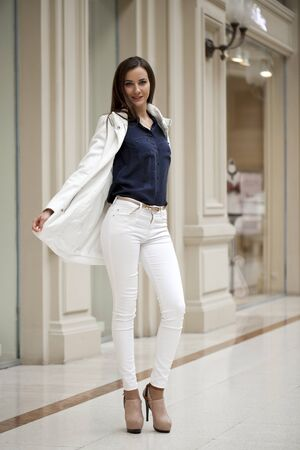 white pants: Young beautiful brunette woman in white pants and jacket and walk the mall Stock Photo