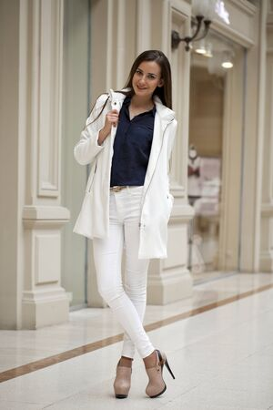 go inside: Young beautiful brunette woman in white pants and jacket and walk the mall Stock Photo