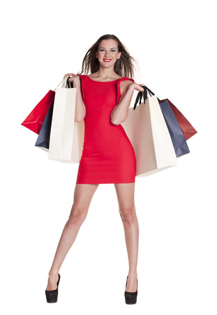 25 30 years women: Fashion woman portrait isolated. White background. Happy girl hold shopping bags. Red dress. female beautiful model