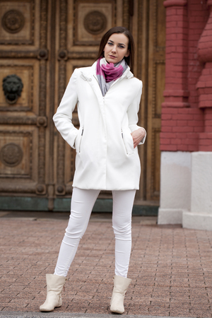 white coat: Portrait in full growth the young beautiful woman in white coat on the background of spring street
