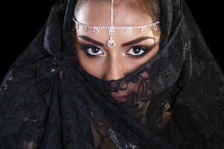 egyptian woman: Portrait of a beautiful woman with arabian makeup in black paranja isolated on dark background Stock Photo