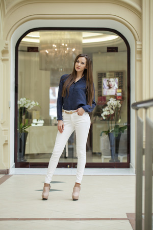 white pants: Young beautiful brunette woman in white pants and blue shirt in the mall