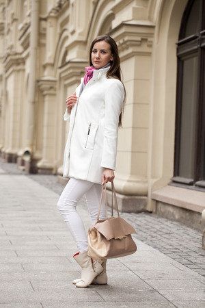 desires 25: Portrait in full growth the young beautiful woman in white coat on the background of spring street