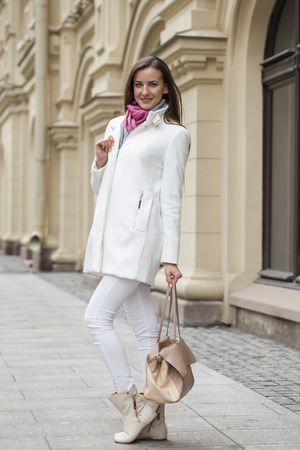 bata blanca: Portrait in full growth the young beautiful woman in white coat on the background of spring street