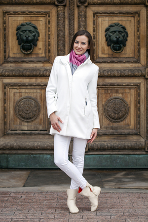 25 30 years: Portrait in full growth the young beautiful woman in white coat on the background of spring street