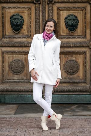 bata blanca: Retrato en pleno crecimiento de la joven y bella mujer en bata blanca en el fondo de la calle del resorte