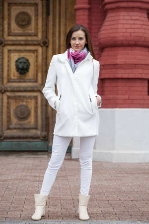 Portrait in full growth the young beautiful woman in white coat on the background of spring street