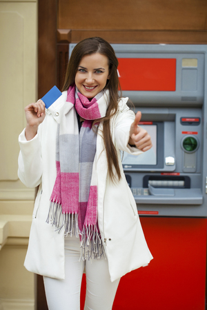 cash slips: Young brunette woman withdrawing money from credit card at ATM