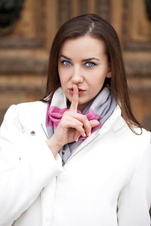 silencio: Retrato de la mujer atractiva morena con el dedo en los labios, el concepto de estudiante mostrar tranquilidad, silencio, gesto secreto, resorte al aire libre