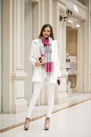 white pants: Fashion portrait of young brunette model posing in shop. Young woman in blue shirt and white pants