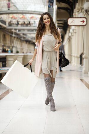 armenian woman: Young beautiful brunette woman in beige dress walking in the shop Stock Photo