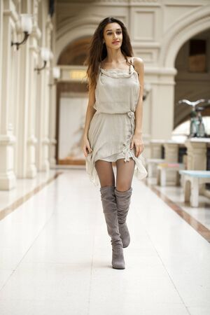 sensual girl: Young beautiful brunette woman in beige dress walking in the shop Stock Photo