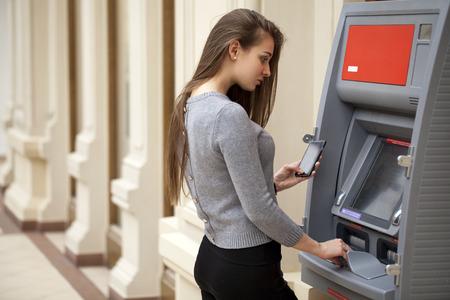 Jonge brunette vrouw die geld van creditcard bij ATM