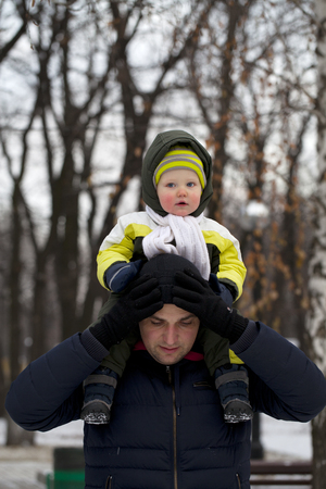 to go sledding: Father and son walking in the park in winter Stock Photo