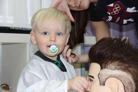 two years: Blonde Little boy cut their hair in a childrens hairdresser, two years baby boy Stock Photo