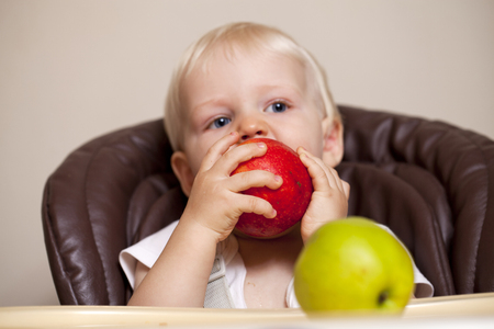 sharpness: sharpness on the apple. Portrait of blonde baby boy sitting at the dinner table