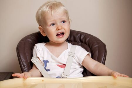 disgruntled: Portrait of blonde baby boy sitting at the dinner table