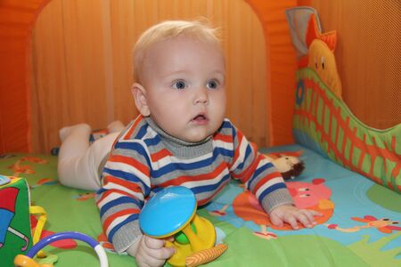 playpen: Baby boy sitting in the orange playpen at home Stock Photo
