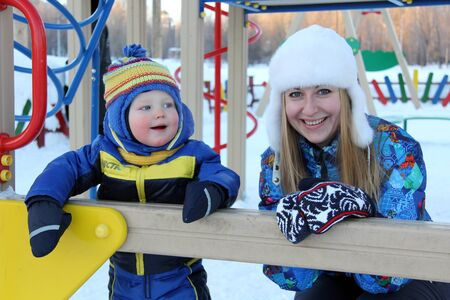 two year old: Beautiful young mother and two year old son in winter park