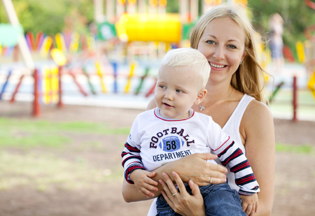 two year old: Beautiful young mother holds on hands of his two year old son in summer park Stock Photo