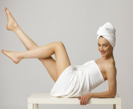 girl  care: Full length portrait of a beautiful young woman wrapped towel isolated on gray background