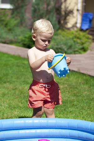 childrens playing: Little boy playing with water near the childrens pool on the lawn in the hot summer Stock Photo
