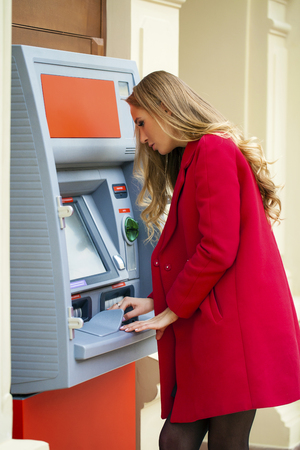 withdraw: Young blonde woman in a red coat withdraw cash from an ATM in a shopping center