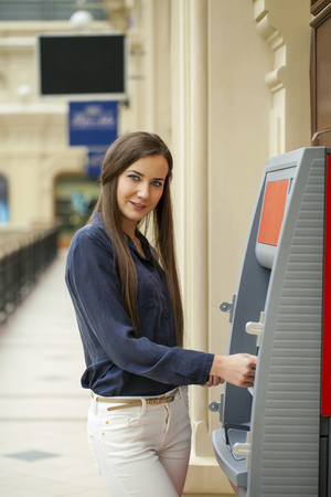 withdrawing: Young brunette woman withdrawing money from credit card at ATM