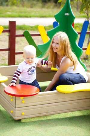 two year old: Young mother with two year old son on the playground Stock Photo