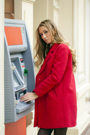 deposit slip: Young blonde woman in a red coat withdraw cash from an ATM in a shopping center