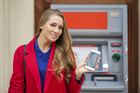 deposit slip: Young blonde woman in a red coat with a phone in his hand on the background of the mall ATM Stock Photo