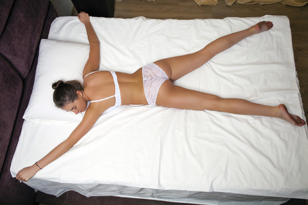Sleeping positions. Young woman in white underwear sleeping on a double bed