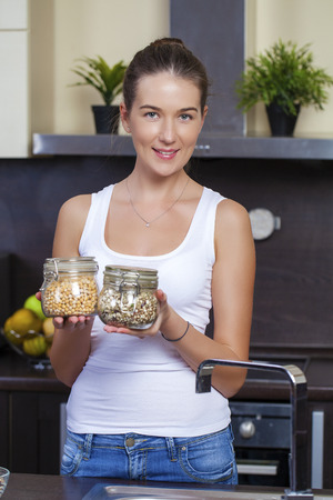 homemaker: Young happy brunette woman holding cans of cereals in the kitchen