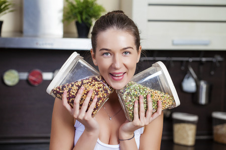 grits: Young happy brunette woman holding cans of cereals in the kitchen