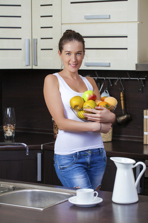 homemaker: Young brunette woman with green apples on a plate on kitchen
