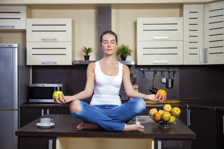 lotus position: Young beautiful woman sitting at the kitchen table in the lotus position