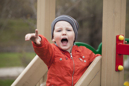 wail: little boy climbing on children playground, spring outdoors Stock Photo