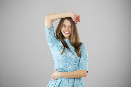 charming girl: Happy beautiful young woman in a turquoise dress on a gray background. Studio portrait Stock Photo