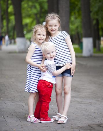 El niño pequeño rubio y dos primos hermanas mayores, reunidos en el parque de verano