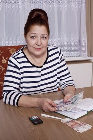 woman holding money: Elderly woman holding money in hand