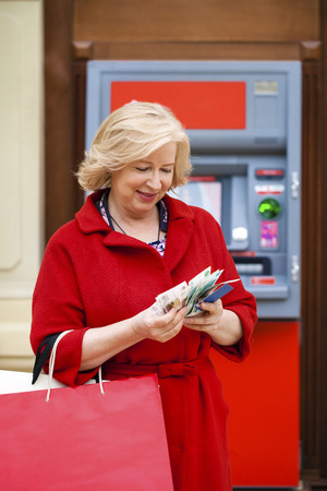 cash slips: Mature blonde woman with shopping bags on the background of the ATM