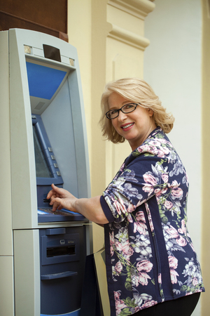 automated teller: Mature blonde woman with credit card in hand near automated teller machine in shop Stock Photo