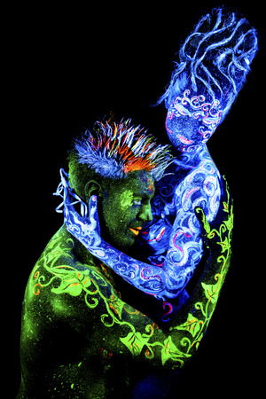 loves: Land Loves Air. Body art glowing in ultraviolet light, four elements, isolated on black background Stock Photo