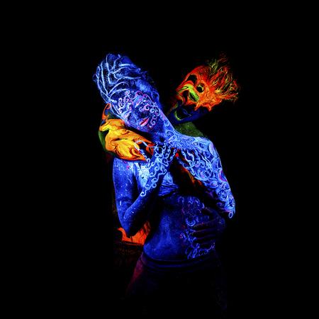 four elements: Fuego y Aire. brillante arte del cuerpo a la luz ultravioleta, cuatro elementos, aislado sobre fondo negro Foto de archivo