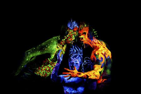 Fuego, tierra y aire. brillante arte del cuerpo a la luz ultravioleta, cuatro elementos, aislado sobre fondo negro Foto de archivo