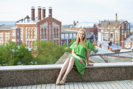 female legs: Portrait in full growth, Young beautiful blonde woman in green dress posing outdoors in sunny weather Stock Photo